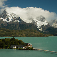 Hosteria Pehoe sits on an island in Lake Pehoe, under the Grand Tower of Paine in Torres del Paine National Park, Chile.