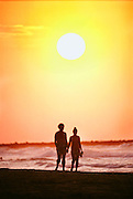 Cartagena, Colombia; a couple walks on the Pacific beach at sunset at Boca Grande.
