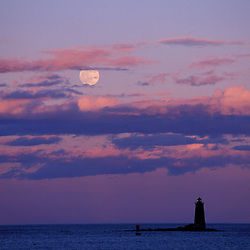A full moon rises behind Whaleback Lighthouse.  New Castle Common, New Castle, NH