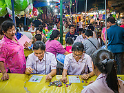 """27 NOVEMBER 2012 - BANGKOK, THAILAND:  School girls play bingo in the Bingo tent at the Wat Saket Temple Fair in Bangkok. Bingo is called Bingo in Thailand. Wat Saket, popularly known as the Golden Mount or """"Phu Khao Thong,"""" is one of the most popular and oldest Buddhist temples in Bangkok. It dates to the Ayutthaya period (roughly 1350-1767 AD) and was renovated extensively when the Siamese fled Ayutthaya and established their new capitol in Bangkok. The temple holds an annual fair in November, the week of the full moon. It's one of the most popular temple fairs in Bangkok. The fair draws people from across Bangkok and spills out in the streets around the temple.   PHOTO BY JACK KURTZ"""