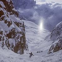 Rare solar refraction off snow flakes. 'le pas de chevres run from les Grands Montets, Chamonix, France. Mont Blanc & Aiguilles de Chamonix bkgd.  Mont Blanc Region, France, skier Jean Franck Charlet.