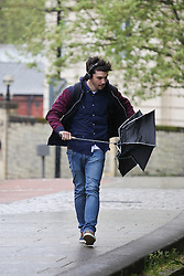 © Licensed to London News Pictures. 05/05/2015. Bristol, Avon, UK. A man unfolding his damaged umbrella in the rain at College Green in Bristol this morning, 5th May 2015. Rain showers and strong, blustery winds have been sweeping up the South West of England, with brighter, but still windy weather expected later. Photo credit : Rob Arnold/LNP