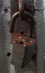 An open rusty metal pad lock hangs on a door