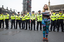 London, UK. 23rd April 2019. A climate change activist stands in front of a police cordon in Parliament Square positioned to prevent fellow activists from Extinction Rebellion from attempting to deliver letters to Members of Parliament requesting meetings to discuss the issue of climate change.