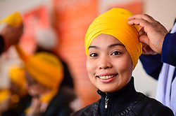 © Licensed to London News Pictures. 27/04/2019. LONDON, UK.  A woman has a turban tired during the festival of Vaisakhi in Trafalgar Square, hosted by the Mayor of London.  For Sikhs and Punjabis, the festival celebrates the spring harvest and commemorates the founding of the Khalsa community over 300 years ago.  Photo credit: Stephen Chung/LNP