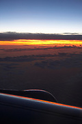 View of airplane wing at sunset flying over an ocean