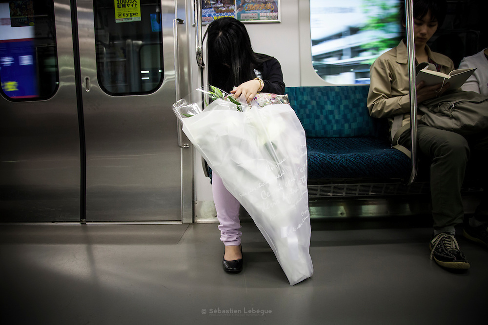 TOKTO, JAPAN, 6 MAY - Portrait of woman sleeping in the train with a very big flowers bouquet in her hands. Her hair cover all her face  that could not permit us to know is identity. May 2012