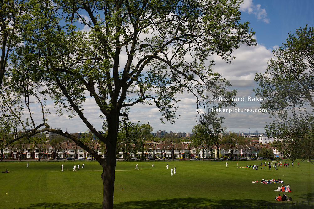 Looking eastwards, a local game of cricket is played beneath 100 year-old mature ash trees on the green grass of Ruskin Park, Lambeth overlooking the city.