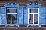 Windows with flowers, village of Listvyanka on southwest shore of Lake Baikal, Siberia, Russia. Typical Siberian log home.
