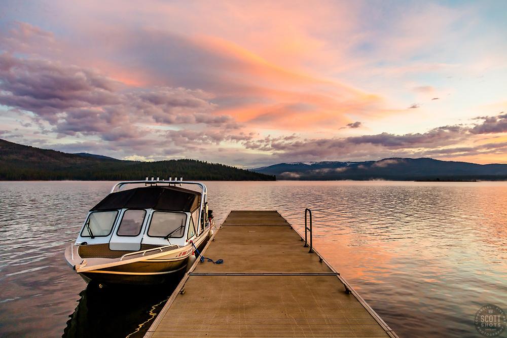 """Stampede Reservoir Sunrise 3"" - Photograph of A fishing boat, dock, and an orange colored sunrise at Stampede Reservoir."