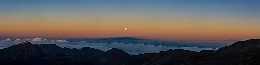 The shadow of Mt. Haleakala extends to the rising full moon.