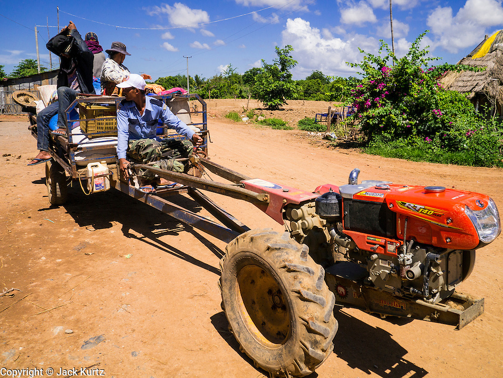 """29 JUNE 2013 - BATTAMBANG, CAMBODIA:   A loaded tractor leaves a rice mill in Reang Keseil near Battambang. The mill is next to the tracks that carry the """"bamboo trains."""" The bamboo train, called a norry (nori) in Khmer is a 3m-long wood frame, covered lengthwise with slats made of ultra-light bamboo, that rests on two barbell-like bogies, the aft one connected by fan belts to a 6HP gasoline engine. The train runs on tracks originally laid by the French when Cambodia was a French colony. Years of war and neglect have made the tracks unsafe for regular trains.  Cambodians put 10 or 15 people on each one or up to three tonnes of rice and supplies. They cruise at about 15km/h. The Bamboo Train is very popular with tourists and now most of the trains around Battambang will only take tourists, who will pay a lot more than Cambodians can, to ride the train.       PHOTO BY JACK KURTZ"""