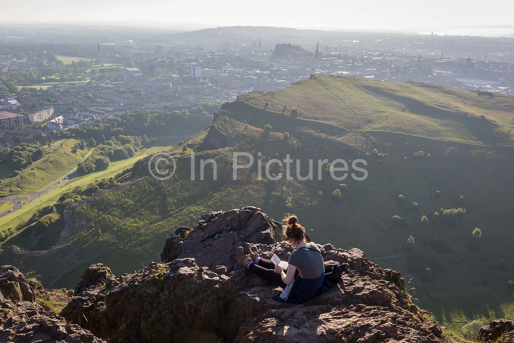 A young woman works with a notebook in summer evening sunshine on the summit of Arthurs Seat in Holyrood Park, overlooking the city of Edinburgh, on 26th June 2019, in Edinburgh, Scotland. Arthurs Seat is an extinct volcano which is considered the main peak of the group of hills in Edinburgh, Scotland, which form most of Holyrood Park, described by Robert Louis Stevenson as a hill for magnitude, a mountain in virtue of its bold design. The hill rises above the city to a height of 250.5 m 822 ft, providing excellent panoramic views of the city and beyond.