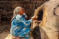 A woman cooking bread in a traditional oven, in a village near the Valley of the Kings, near Luxor, Egypt