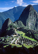 "The pinnacle of Huayna Picchu rises over Machu Picchu, a magnificent Inca archeological site in the Cordillera Vilcabamba, Andes mountains, Peru, South America. The Incas built temples, terraces, and a trail up the peak of Huayna Picchu (""Young Peak"" in Quechua, 2720 meters or 8920 feet above sea level). Machu Picchu was built around 1450 AD as an estate for the Inca emperor Pachacuti (14381472). Spaniards passed in the river valley below but never discovered Machu Picchu during their conquest of the Incas 1532-1572. The outside world was unaware of the ""Lost City of the Incas"" until revealed by American historian Hiram Bingham in 1911. Machu Picchu perches at 2430 meters elevation (7970 feet) on a well defended ridge 450 meters (1480 ft) above a loop of the Urubamba/Vilcanota River ( Sacred Valley of the Incas). UNESCO honored the Historic Sanctuary of Machu Picchu on the World Heritage List in 1983."