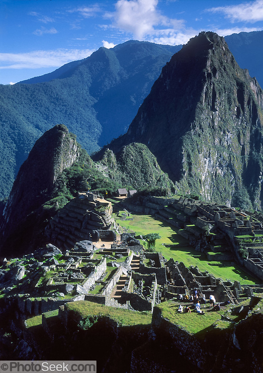 """The pinnacle of Huayna Picchu rises over Machu Picchu, a magnificent Inca archeological site in the Cordillera Vilcabamba, Andes mountains, Peru, South America. The Incas built temples, terraces, and a trail up the peak of Huayna Picchu (""""Young Peak"""" in Quechua, 2720 meters or 8920 feet above sea level). Machu Picchu was built around 1450 AD as an estate for the Inca emperor Pachacuti (14381472). Spaniards passed in the river valley below but never discovered Machu Picchu during their conquest of the Incas 1532-1572. The outside world was unaware of the """"Lost City of the Incas"""" until revealed by American historian Hiram Bingham in 1911. Machu Picchu perches at 2430 meters elevation (7970 feet) on a well defended ridge 450 meters (1480 ft) above a loop of the Urubamba/Vilcanota River ( Sacred Valley of the Incas). UNESCO honored the Historic Sanctuary of Machu Picchu on the World Heritage List in 1983."""
