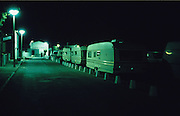 Europe, France, Camargue, Saintes Maries de la Mer, Gypsy Pilgrimmage 'Pelerinage des Gitans aux Saintes Maries de la Mer'. Gypsy caravans parked alongside the road at midnight. Gypsies from all over the world come to celebrate their patron Saint Sara who is carried by them from the church to the sea-shore. May 24th and 25th every year.