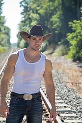 good looking cowboy on railroad tracks