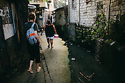 Houses in this informal settlement are packed close together, separated by narrow alleys and rough concrete drains. The midwife knows the general location of the house but has to pause every so often to ask for directions.