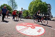Een jongen fietst door waar het voetgangersgebied begint. In Utrecht worden fietsers gewezen op een andere route. Vanaf 1 mei mogen fietsers gedurende het grootste deel van de dag niet meer door een deel van het centrum fietsen. Het voetgangersgebied is fors uitgebreid.<br /> <br /> A big painted sign on the road suggest cyclists another route to ride at the city center in Utrecht. A part of the center is closed for cyclists for the main part of the day.