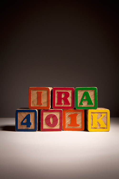 Stacked children's blocks spelling IRA and 401K sitting on table