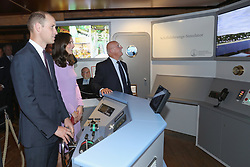 The Duchess of Cambridge watches as the Duke of Cambridge takes the wheel of a ship simulator during their visit to the Maritime Museum in Hamburg, Germany.