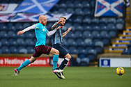 Liam Boyce (#10) of Heart of Midlothian FC gets to the ball ahead of Iain Davidson (#4) of Raith Rovers FC during the SPFL Championship match between Raith Rovers and Heart of Midlothian at Stark's Park, Kirkcaldy, Scotland on 30 April 2021.