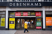 A woman walks past the Folkestone Debenhams store in the final few days of the 'Everything Must Go' sale before closing down on 13th Jauary 2020 in Folkestone, Kent. United Kingdom. The company announced the closure of 19 stores across the UK after going into administration in 2019.