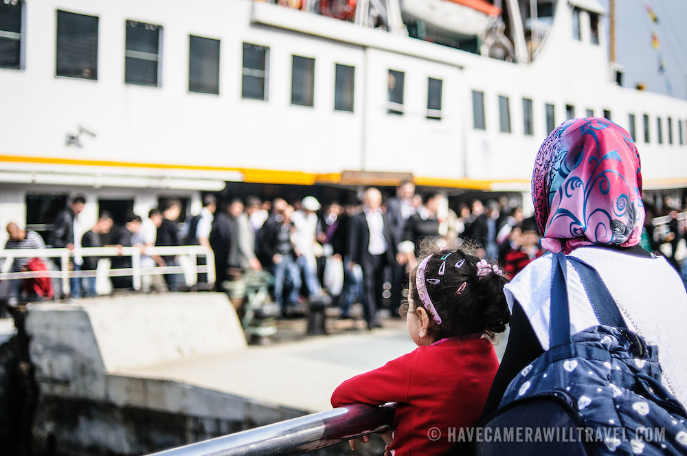 A mother and young daughter wait for the arriving ferry in Istanbul's Eminonu district of the Golden Horn waterfront in Istanbul