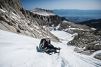 Hiker takes a rest on snowy chute on Mountaineers Route of Mount Whitney, Sierra Nevada Mountains, California