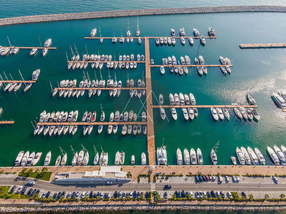 Aerial view of Marina d'Arechi port, a big pontoon with sailing yacht along the shoreline, Salerno, Italy.