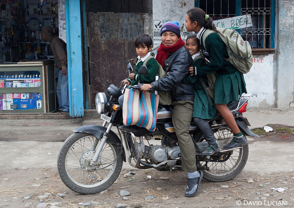 A man sitting with his children on his motorbike along a street in Pasighat.