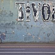Bicycle left against the wall near the entrance to Tivoli Gardens and the famous Tivoli sign in Copenhagen, Denamrk