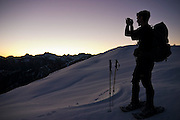 Dallas Anderson pauses to photograph the sunrise on an early morning climb of Snow King Mountain, Glacier Peak Wilderness, Washington.