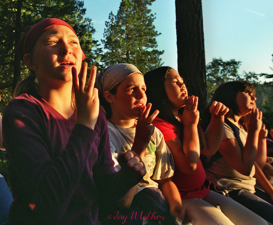"""Girl Scouts, bathed in the lingering glow of sunset, use sign language while they sing a campfire song at Camp Menzies.  The song, """"Moon on the Meadow,"""" reflects upon a time when Native Americans were the original inhabitants of the land whre the camp now exists. The group let ro right: Erin Nash, 10, from San Jose; Kassi Branscom, 10, from Modesto; Alex Norris, 9, from San Jose; Samantha Baxter, 10, from Carmichael.  June 27, 2000.  Sacramento Bee/Jay Mather."""