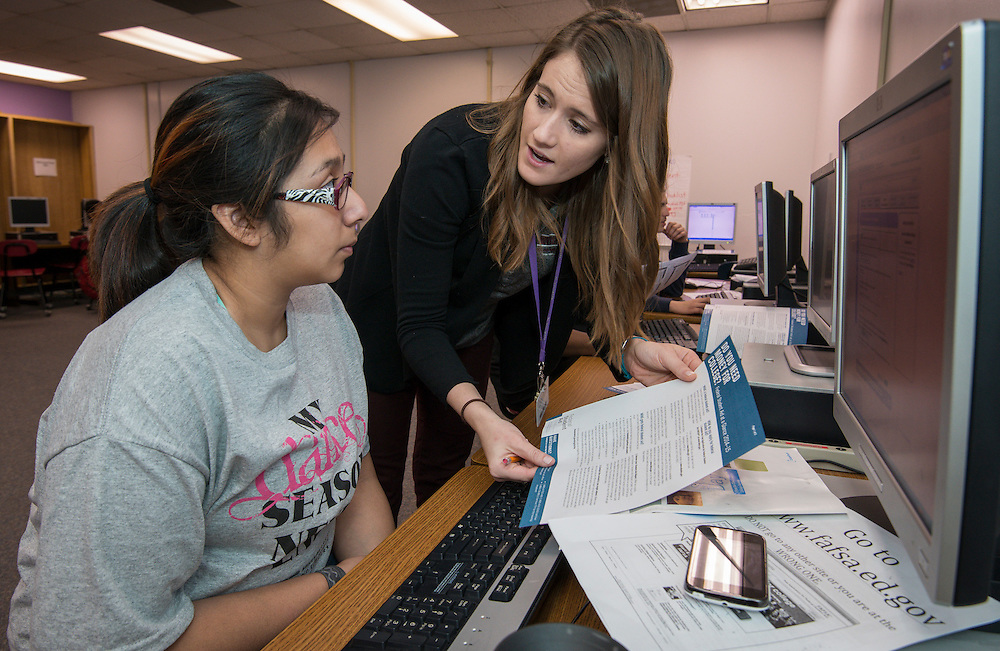 AdviseTexas volunteer Kali Nunnelly helps students register for financial aid on National FAFSA Day at Davis High School, February 20, 2014.