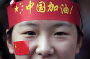 "A woman wears a headband reading ""Go China"" and a flag sticker on her face at the Olympic Torch relay in the southern city of Wuhan, China."