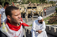 Muslim Brotherhood supporters stand infront of military vehicles outside Nassr City in Cairo.