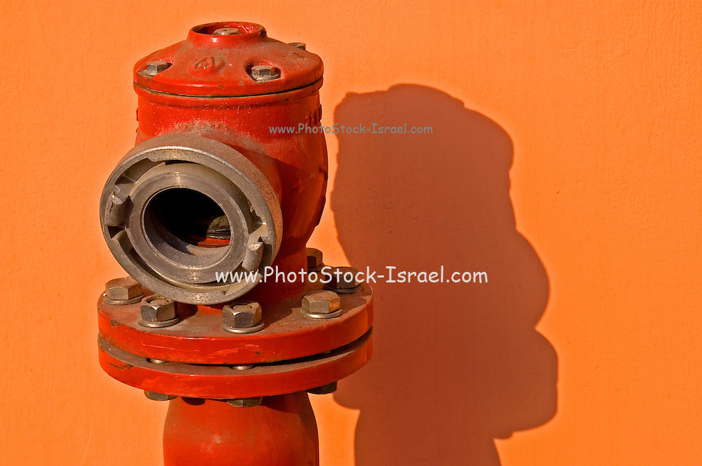 red fire hydrant for fire prevention and immediate reaction to fire hazard on an orange background