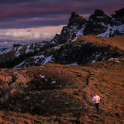 Mountain runner running on a ridge high in the mountains after sunset near Lake Tahoe, CA.