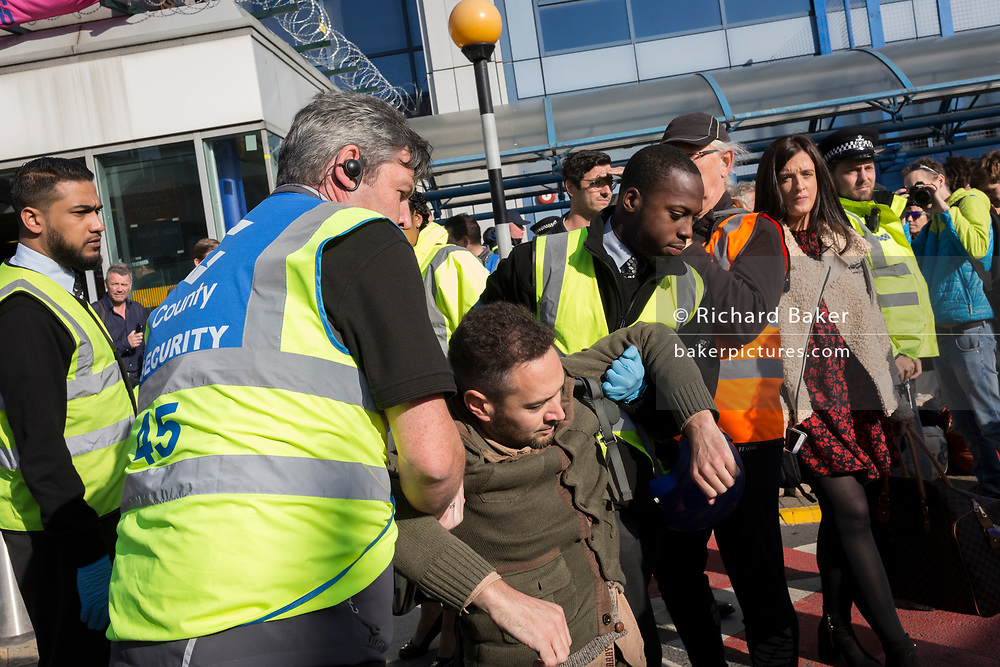 An environmental activist is arrested under the Public Order Act while protesting about Climate Change during the occupation of City Airport (London's Business Travel hub) in east London, the fourth day of a two-week prolonged worldwide protest by members of Extinction Rebellion, on 10th October 2019, in London, England.
