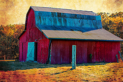 This aged red barn stands proud and tall showing signs of age and weather with a timeless and antique feel.