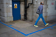 A man wearing blue trousers walks past a blue line designed to give directions at Tower Bridge in London, United Kingdom. (photo by Mike Kemp/In Pictures via Getty Images)