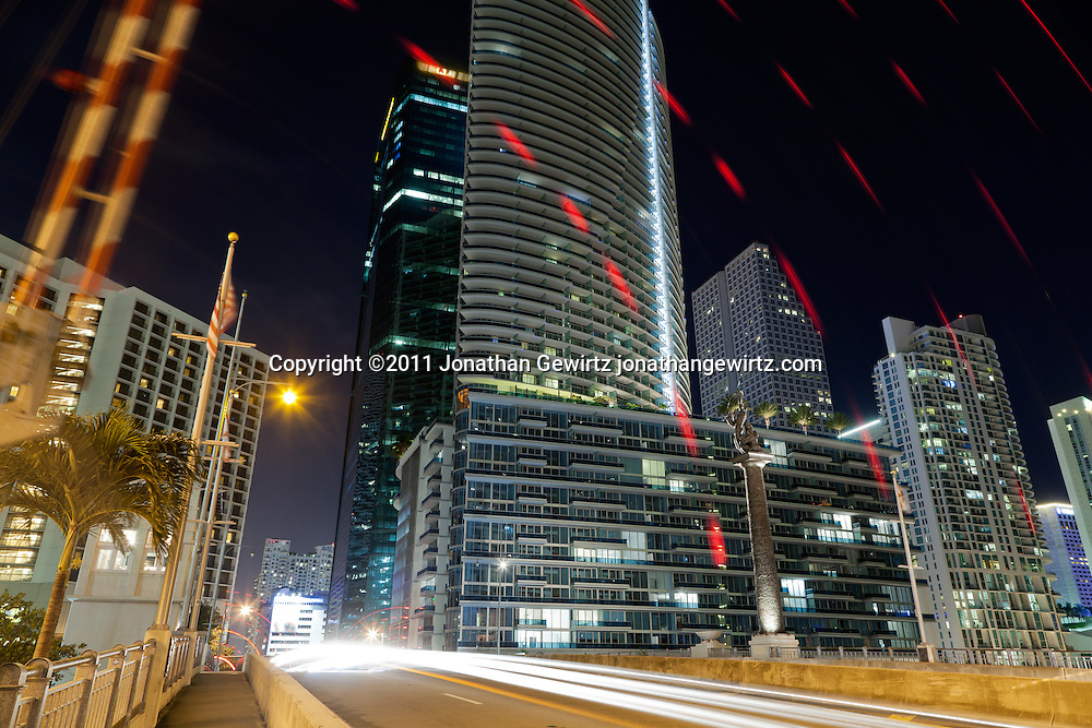 Night view of the Brickell Avenue drawbridge over the Miami River as the pedestrian gate goes up, with condo and office buildings. WATERMARKS WILL NOT APPEAR ON PRINTS OR LICENSED IMAGES.