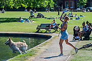 A woman exercises her dog in the model boating lake - people enjoy the sun on Clapham Common after the Government eased restrictions and allowed people to meet - Lambeth Council have replaced signs to say stay alert and to allow people sit on benches. The 'lockdown' continues for the Coronavirus (Covid 19) outbreak in London.
