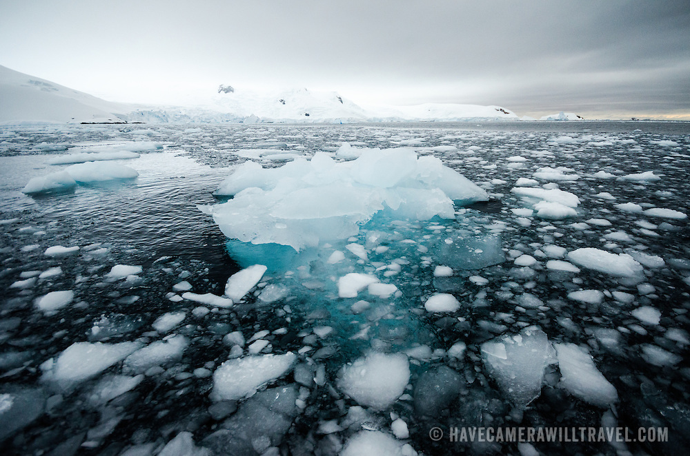 Small pieces of ice and brash ice float on the water of Curtis Bay, Antarctica. Because the salty sea water temperature is at or below the freezing temperature of the freshwater ice, the ice remains frozen for long periods of time.