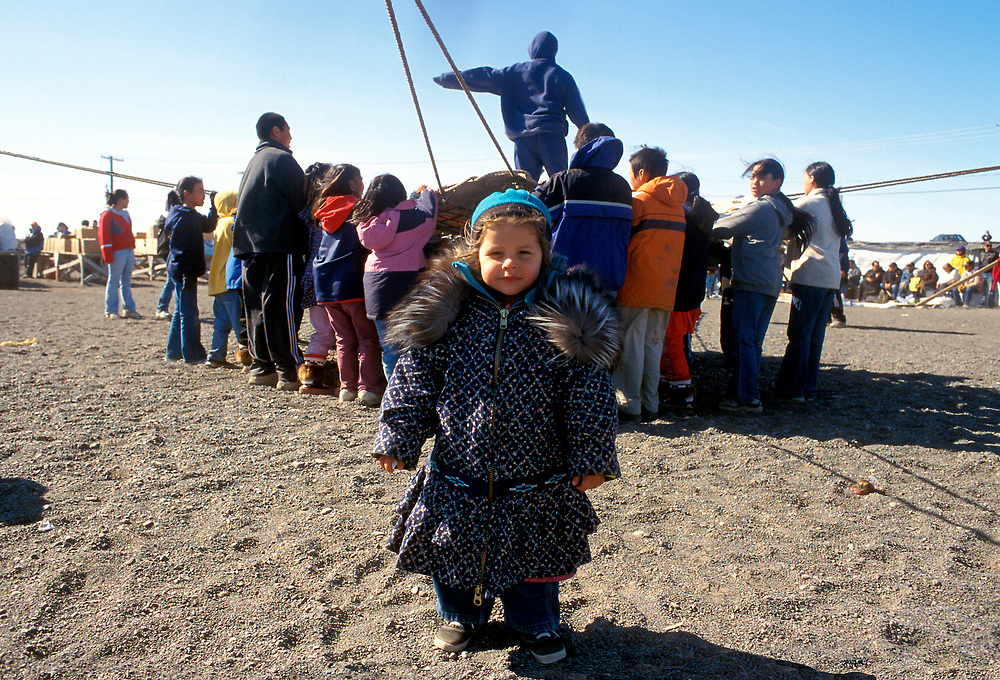 Alaska. Barrow. A child wearing an traditional parka walks away from the blanket toss activities of the Inupiat people.