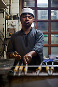 A man makes and griddles kebabs at Karims Restaurant, Old Delhi