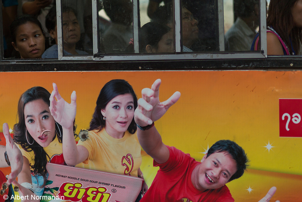 Crowded commuter bus in traffic with famous movie stars painted on side of bus advertising
