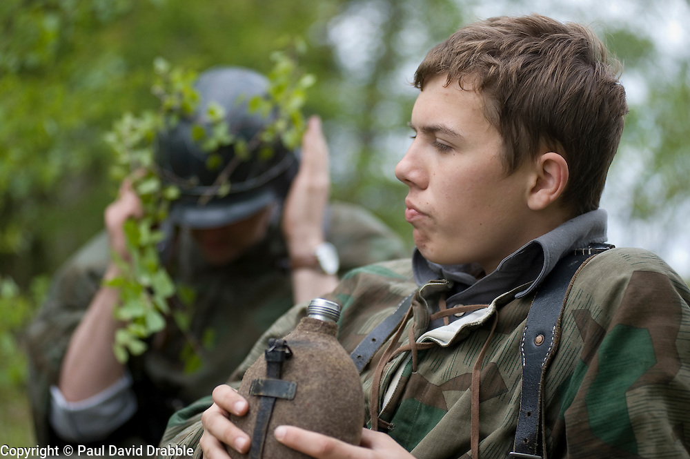 Reenactors from Northern World War Two Association, dressed as panzer grenadiers from the elite Grossdeutschland division, take a break during a private 24hr exercise, held at Sutton Grange, near Ripon in Yorkshire 15  May 2010<br /> Images © Paul David Drabble.